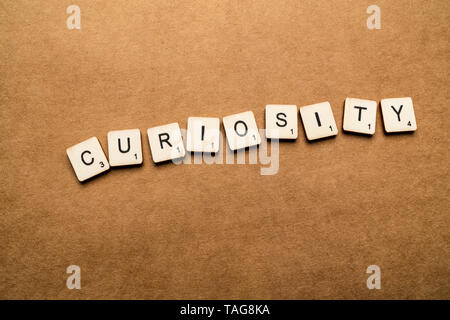 LONDON, UK - May 24 2019: The word CURIOSITY, spelt with wooden letter tiles over a brown textured background - Stock Photo