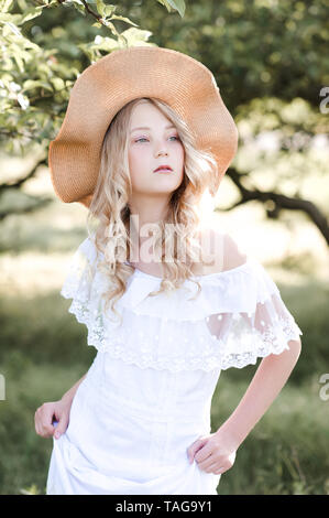 Beautiful blonde girl 16-17 year old wearing white stylish dress and hat walking in park. Romance. - Stock Photo