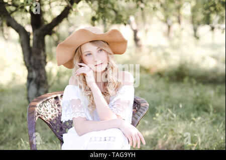 Pretty blonde teenage girl 16-18 year old wearing hat and elegant white dress outdoors. Summer time. - Stock Photo