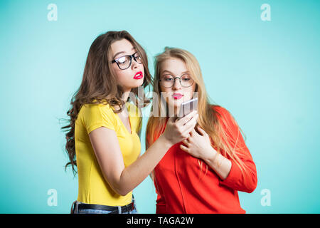 Two beautiful women holding a smartphone, seriously looking at it. Technologies, new products. - Stock Photo