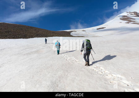 A group of tourists with backpacks goes hiking on a snowy mountain - Stock Photo