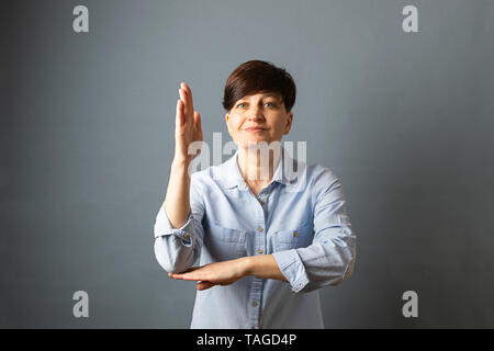 Portrait of a young woman with a short hair cut hands up on a gray empty background. Human emotions facial expression - Stock Photo