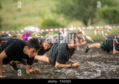 SOFIA, BULGARIA - JULY 7th 2018: men crawling under barbed wire to overcome obstacle in a mud race - Stock Photo