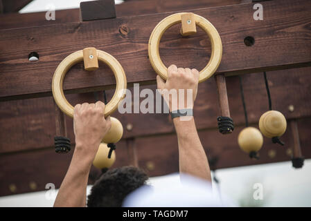 SOFIA, BULGARIA - JULY 7th 2018 - a man is hanging on gymnastics rings in a strength competition - Stock Photo