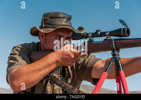 A close-up of a professional hunter taking aim at a target on a game farm in Namibia. - Stock Photo