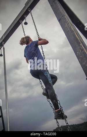 SOFIA, BULGARIA - JULY 7th 2018 - a woman is climbing a hanging metal leddar ina strength run - Stock Photo