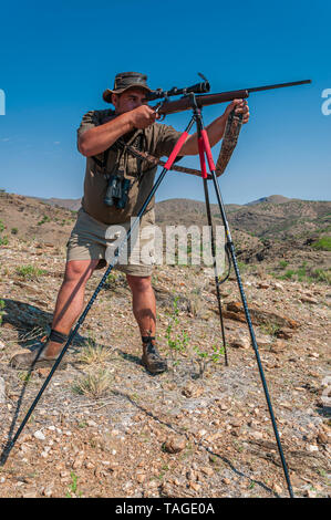 A professional hunter is taking aim on a target taken on a game farm in Namibia. - Stock Photo