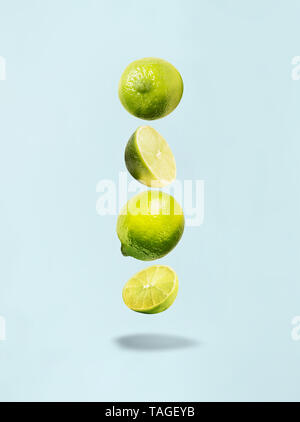 Flying lime on blue background with shadow. Healthy food. - Stock Photo