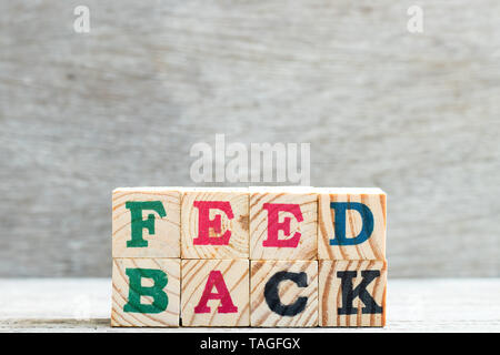 Letter block in word feedback on wood background - Stock Photo