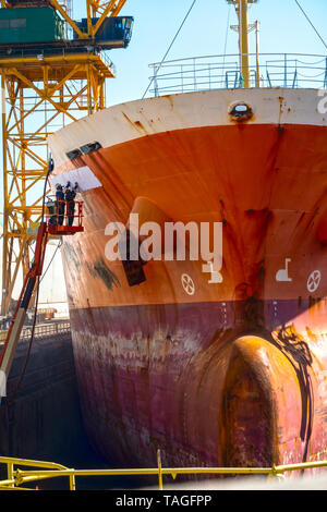 Cleaning and repainting of hulls of a big ship or big ship being fixed in a shipyard or big ship being repaired and painted in a dry dock or vessel - Stock Photo