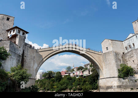 MOSTAR, BOSNIA AND HERZEGOVINA - AUGUST 05, 2015: Tourist and locals walking over Old bridge in Mostar.The bridge is included to the UNESCO heritage - Stock Photo