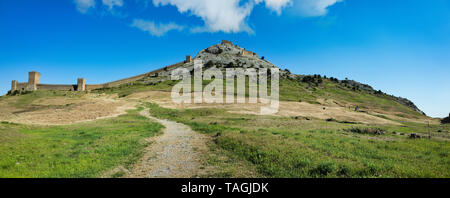 Genoese fortress in Sudak, Crimea. Panorama view of ruins of ancient historic castle or fortress on crest of mountain near sea. Beautiful summer touri - Stock Photo