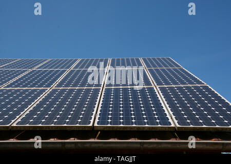 solar panel soak up the blue sky sun, modern solar cells or photovoltaic on the roof of an old woodshed with new gutter in front of azure sky - Stock Photo