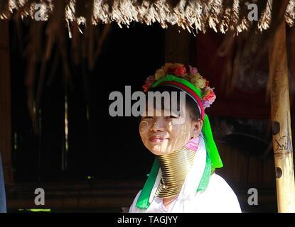 LONGNECK KAREN VILLAGE, THAILAND - DECEMBER 17. 2017: Long neck woman sitting in front of a hut - Stock Photo