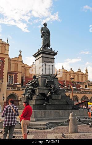 Visitors at the statue of Adam Mickiewicz.  Main Market Square, Krakow.  Old city.  Rynek Glowny. - Stock Photo