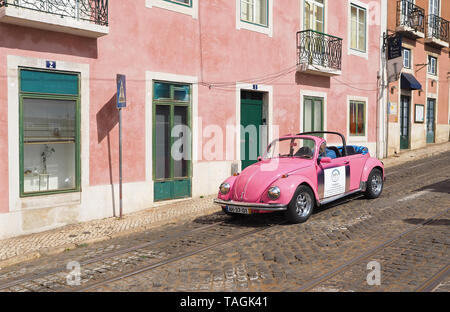 Pink VW beetle in Lisbon in Portugal - Stock Photo