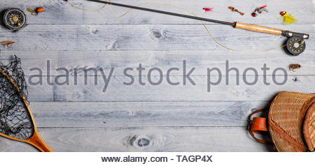 Fly fishing equipment overhead on wooden background with copy space - Stock Photo