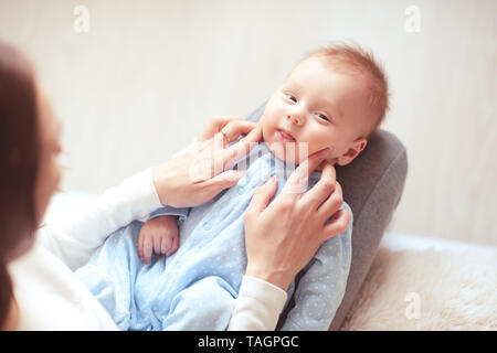 Funny baby boy lying on mother hands close up. Looking at camera. Maternity. Top view. - Stock Photo