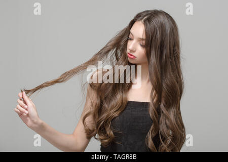 Fashion woman, hair confusion. Long wavy hair and makeup - Stock Photo