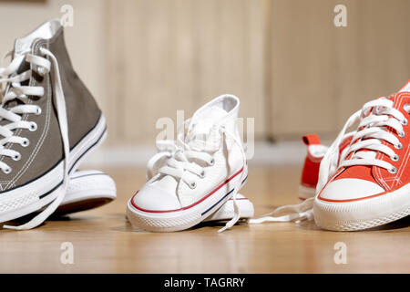 Conceptual image of gumshoes sneakers shoes of father mother and son daughter family on wood floor in different sizes in Sweet home togetherness Happy - Stock Photo