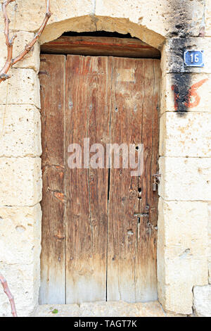 A very old weathered arched wooden door with a metal wrought-iron lock and embedded in an old wall made of shell rock. - Stock Photo