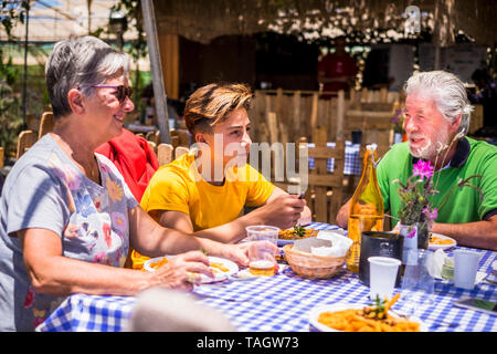 Active senior aged old people with grandson having lunh together outdoor in alternative restaurant - family concept with teenager and grandfathers tog - Stock Photo