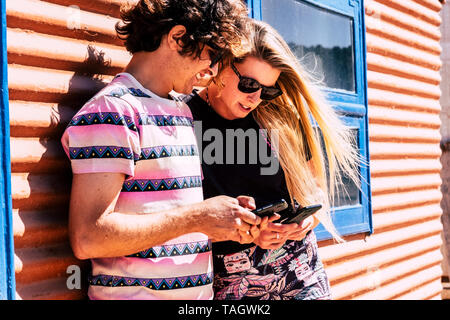 Millennial hipster beautiful young people caucasian couple using and looking eachother cellular phone in outdoor day of sun smiling and having fun - h - Stock Photo