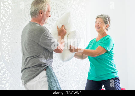 Playful senior old caucasian people couple play at home with pillows making war and having lot of fun together - happy retired lifestyle for men and w - Stock Photo