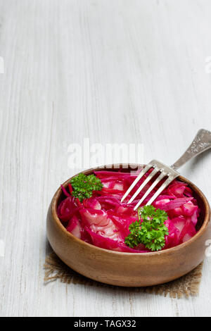 Salad  with cabbage and beetroot in wooden bowl on white table - Stock Photo