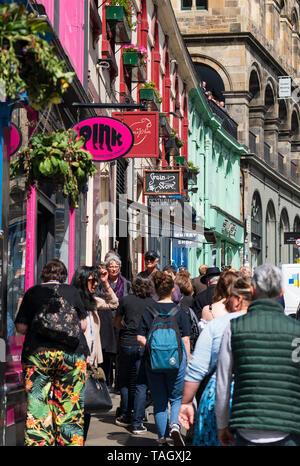 Tourists walking past shops on historic Victoria Street in Edinburgh Old town, Scotland, UK - Stock Photo