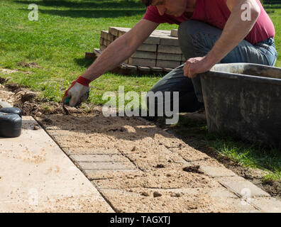 Laying gray concrete paving slabs in house courtyard driveway patio. Professional worker, sand foundation base. - Stock Photo