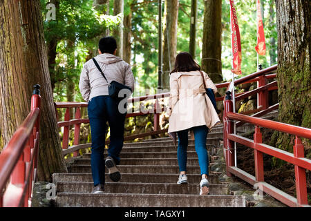 Nikko, Japan - April 4, 2019: Couple tourists walking on red stone steps stairs up in Tochigi prefecture in mountain forest leading to Toshogu shrine