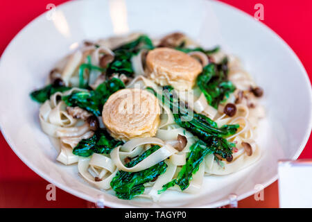 Noodles closeup on plate traditional Japanese cuisine display with local famous tofu skin dish and green spinach - Stock Photo