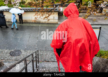 Man in red poncho walking down steps during rainy day on street road sidewalk near Gion and fallen cherry blossom flower petals - Stock Photo