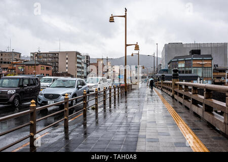Kyoto, Japan - April 9, 2019: Gojo-dori street bridge near Gion district during rainy cloudy day and many cars in traffic with view of sidewalk - Stock Photo