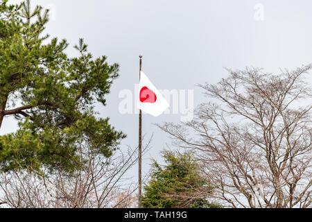 Takayama, Japan Hida no Sato old folk village closeup of Japanese red and white flag isolated against sky on flagpole pole - Stock Photo
