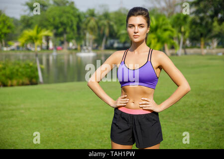 Young and beautiful woman is ready for her fitness workout in the park - Stock Photo