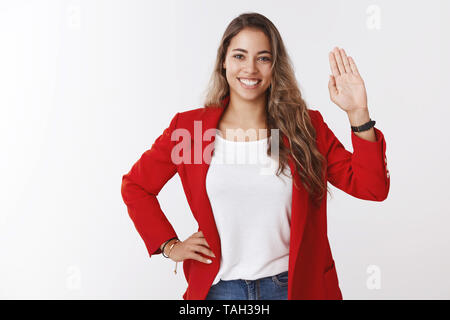 Friendly-looking confident attractive young european curly-haired 25s woman wearing red jacket waving raised palm hello welcome gesture smiling - Stock Photo