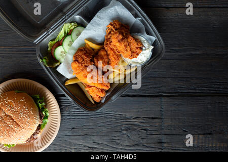 Hamburger, french fries and fried chicken in takeaway containers on the wooden background. Food delivery and fast food concept - Stock Photo
