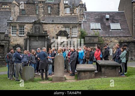 Tourists on a walking tour of Edinburgh's visit the grave of John Gray, the master of Greyfriars Bobby, in Greyfriars Kirkyard. - Stock Photo