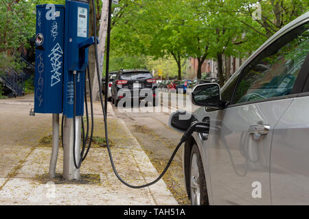 Montreal, CA - 25 May 2019: Chevrolet Volt electric car plugged into an EV charging station. - Stock Photo
