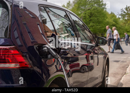 Montreal, CA - 25 May 2019: Electric car plugged into an EV charging station. - Stock Photo