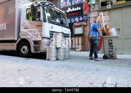 Man taking out a trash bin in front of a stack of empty beer kegs on the street in front of a beer delivery truck in Madrid, Spain. - Stock Photo