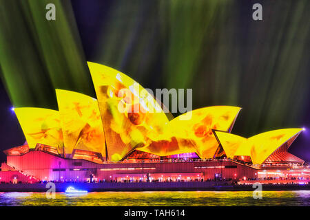 Sydney, Australia - 25 May 2018: Yellow fading light painted image of tiled sails of the SYdney Opera house under yellow streams of light in dark sky  - Stock Photo