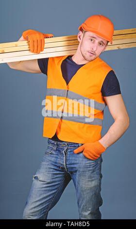 Carpenter, woodworker, labourer, builder on confident face carries wooden beams on shoulder. Man in helmet, hard hat and protective gloves holds wooden beam, grey background. Hardy labourer concept. - Stock Photo