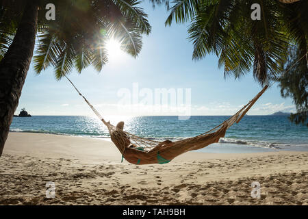 Woman Lying On The Hammock Between The Palm Trees In Front Of Sea At Beach - Stock Photo