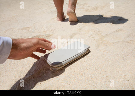 Close-up Of A Man Taking Woman's Lost Purse On Sand At Beach - Stock Photo