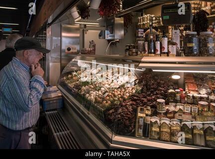 Man looking at fresh market produce stall in Mercado de la Ribera indoor market, Bilbao, Basque Country, Spain - Stock Photo