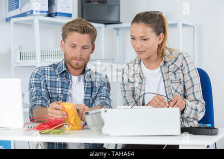 coworkers using multimeter to test electrical appliance - Stock Photo