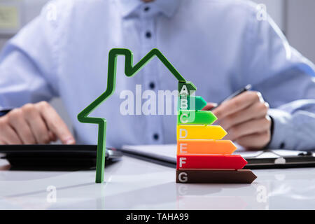 House With Energy Efficiency Rate In Front Of Businesspeople Working On Documents - Stock Photo